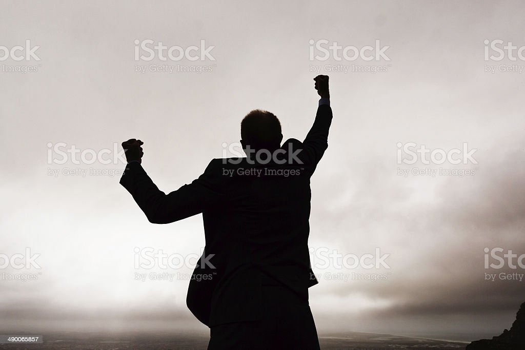 Desperate man on mountainside, silhouetted against dark clouds stock photo