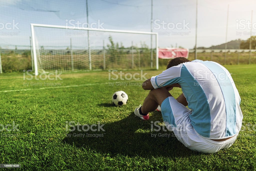 Desperate soccer player on the football pitch stock photo