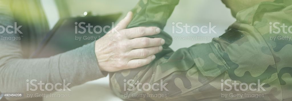 Desperate soldier with civil friend stock photo