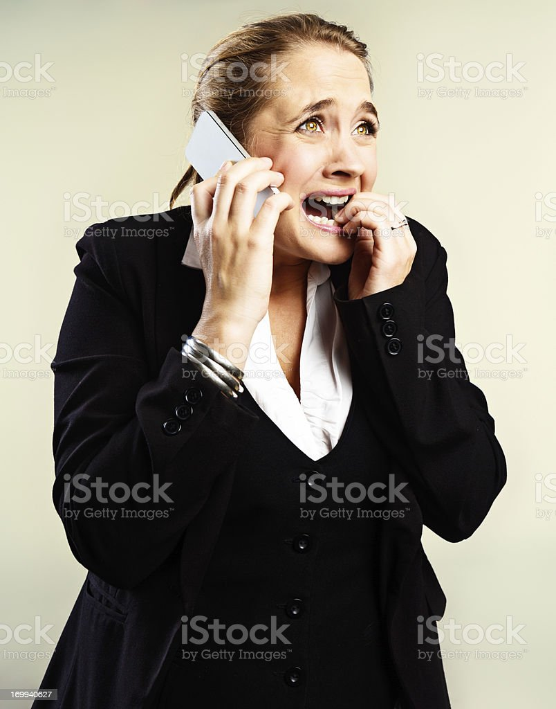 Desperate, stressed businesswoman on phone bites nails in panic stock photo