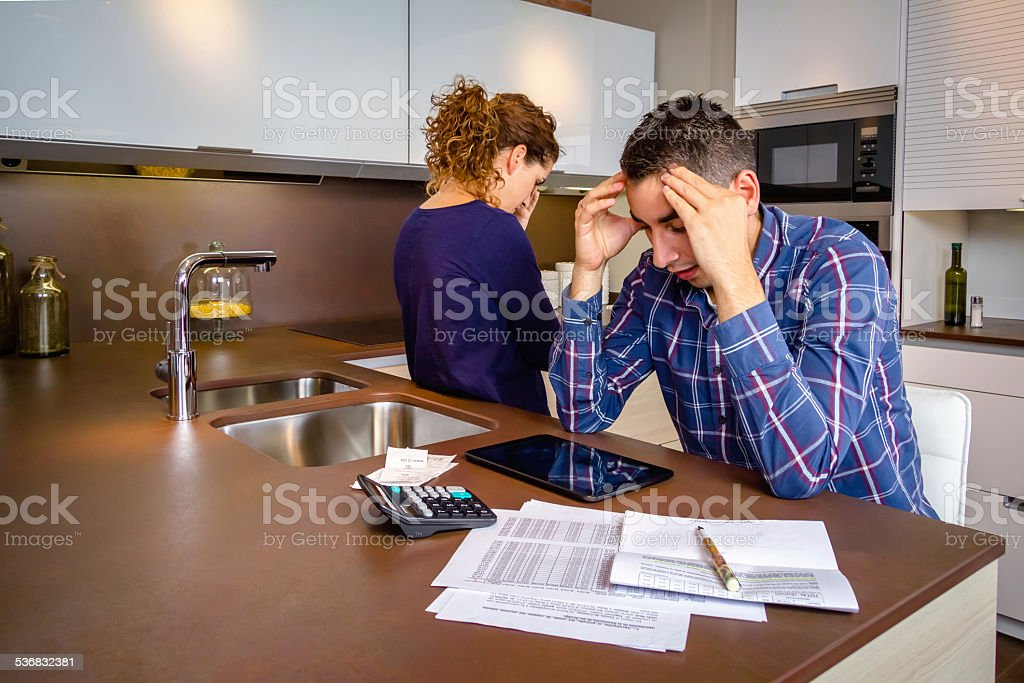 Desperate young couple with debts reviewing their bills stock photo