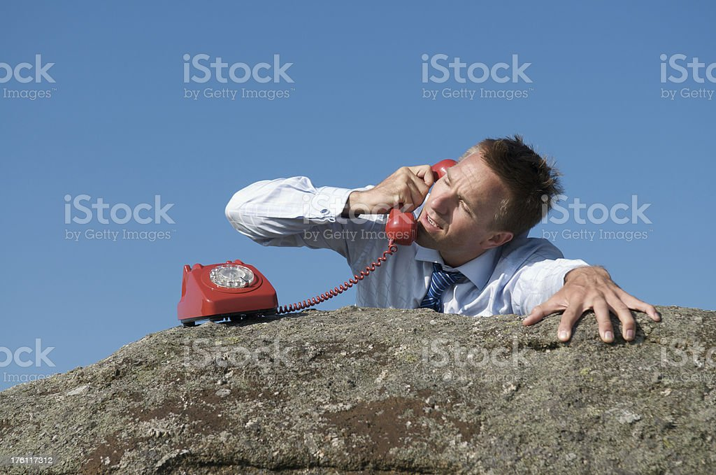 Desperate Young Man Businessman Clinging to Rock Talking Red Phone royalty-free stock photo