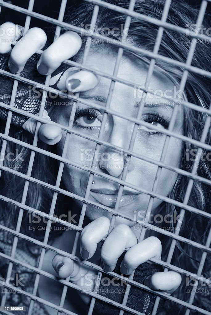 Desperate young woman in jail royalty-free stock photo