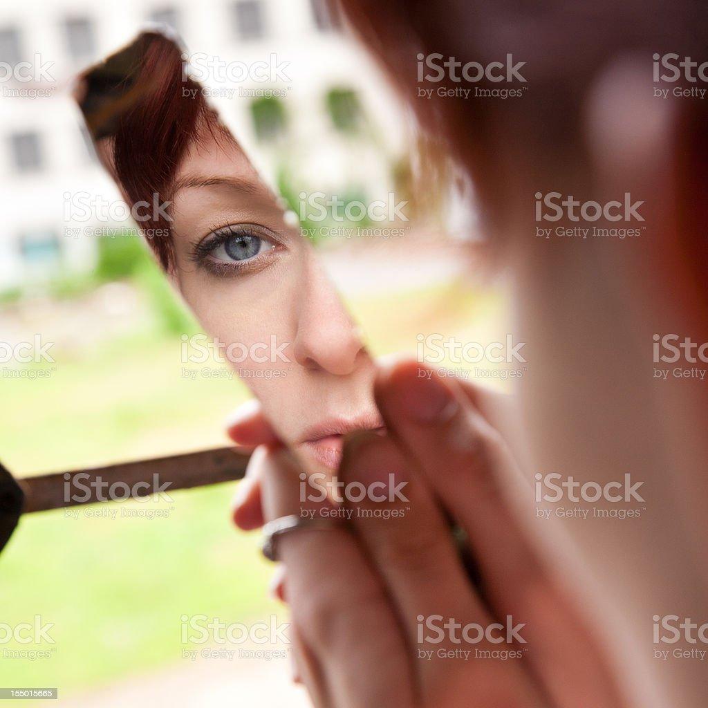 Desperate Young Woman Looking into broken mirror stock photo