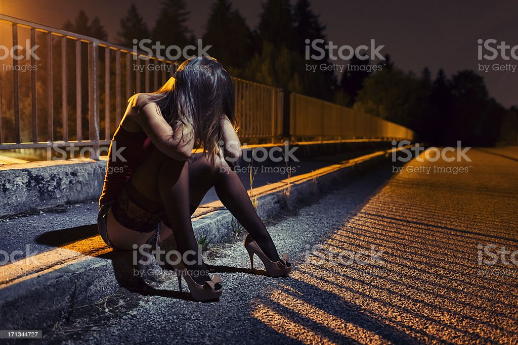 Desperate young woman sitting on the bridge stock photo