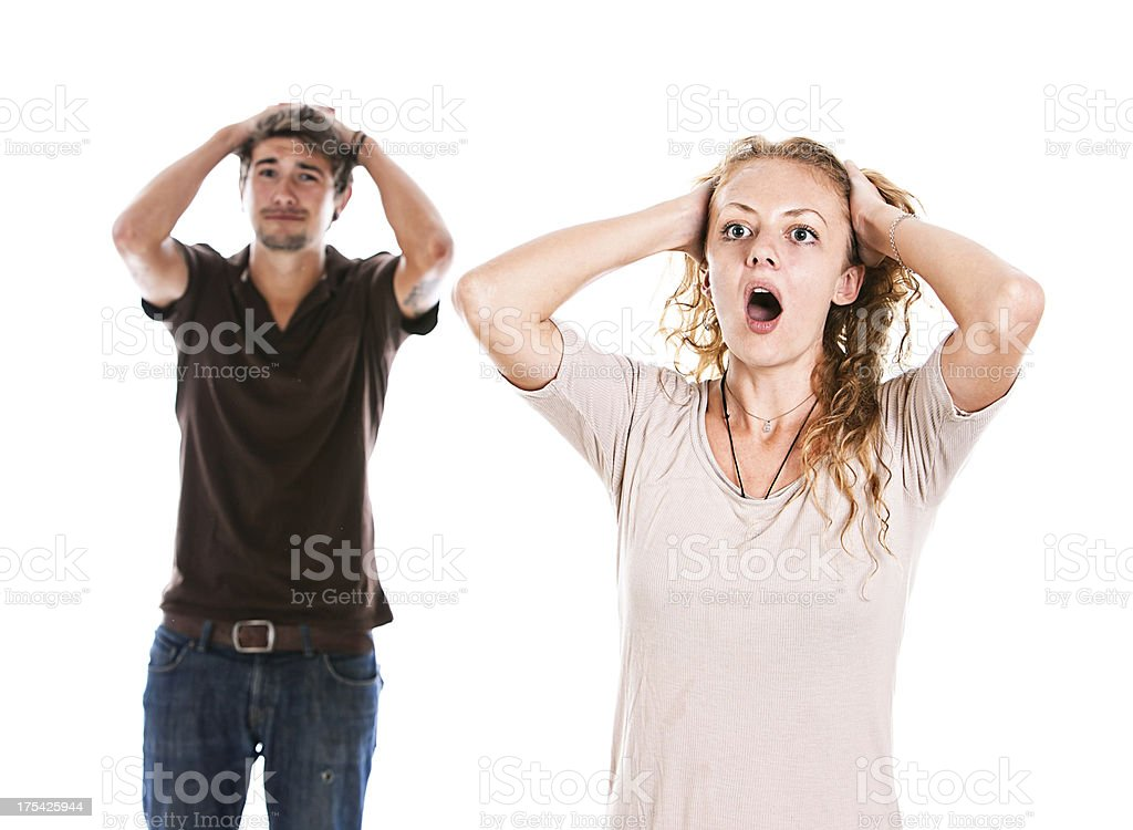 Desperate-looking young couple hands to their head looking shocked stock photo