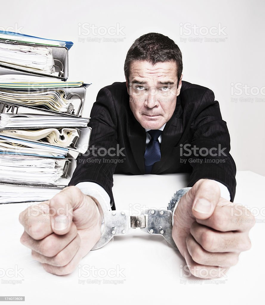 Desperately overworked handcuffed businessman is a real wage slave royalty-free stock photo