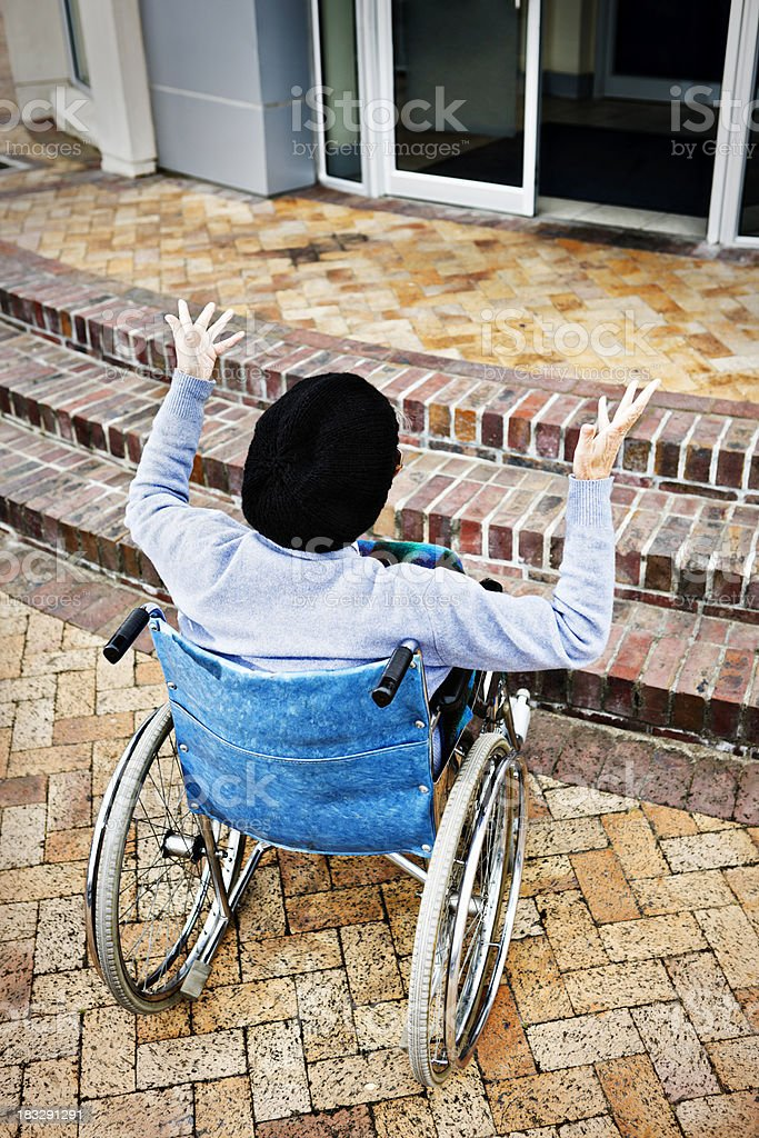 Desperation as wheelchair bound woman faces steps with no ramp royalty-free stock photo