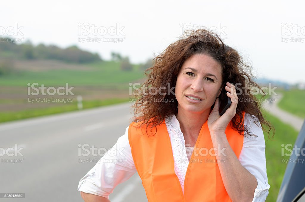 Despondent female driver trying to summon help stock photo
