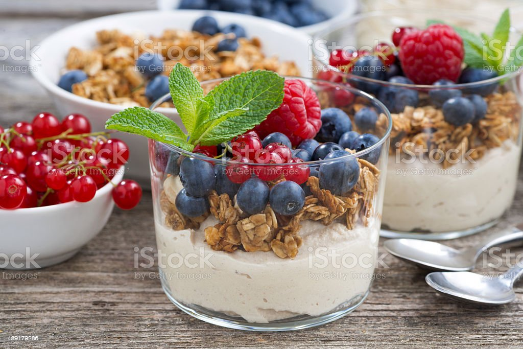 dessert with sweet cream, fresh berries and granola, closeup stock photo