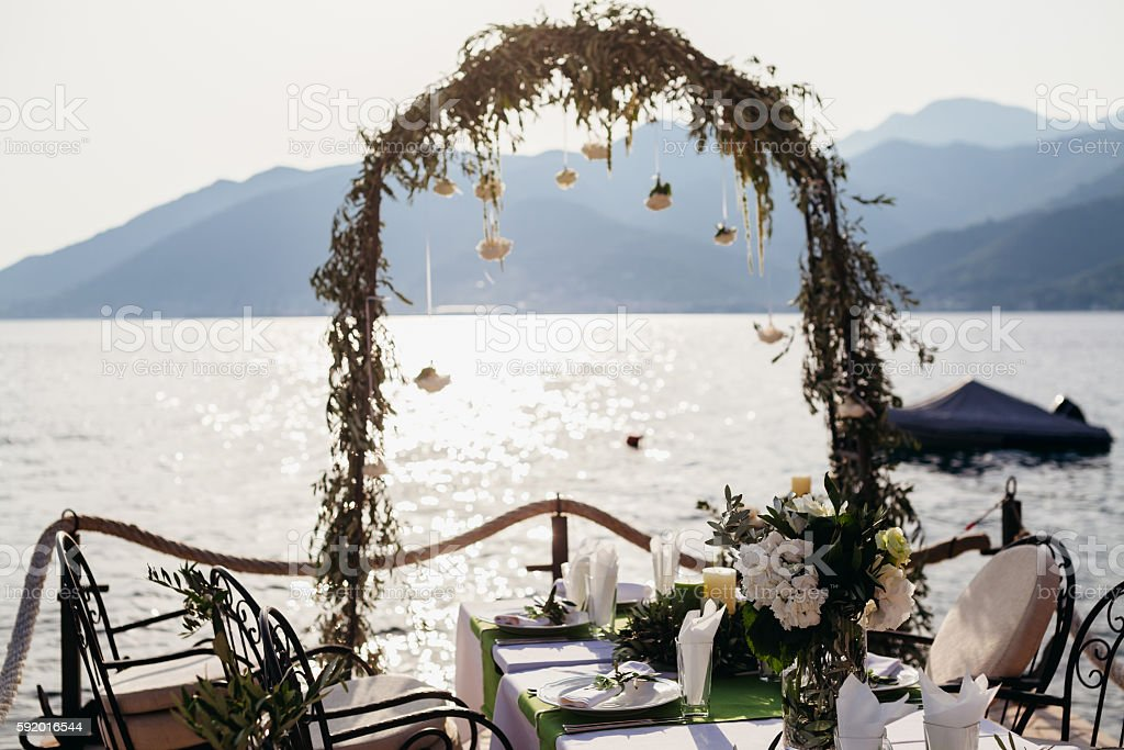 destination wedding arch and banqouet covered table at sunset stock photo