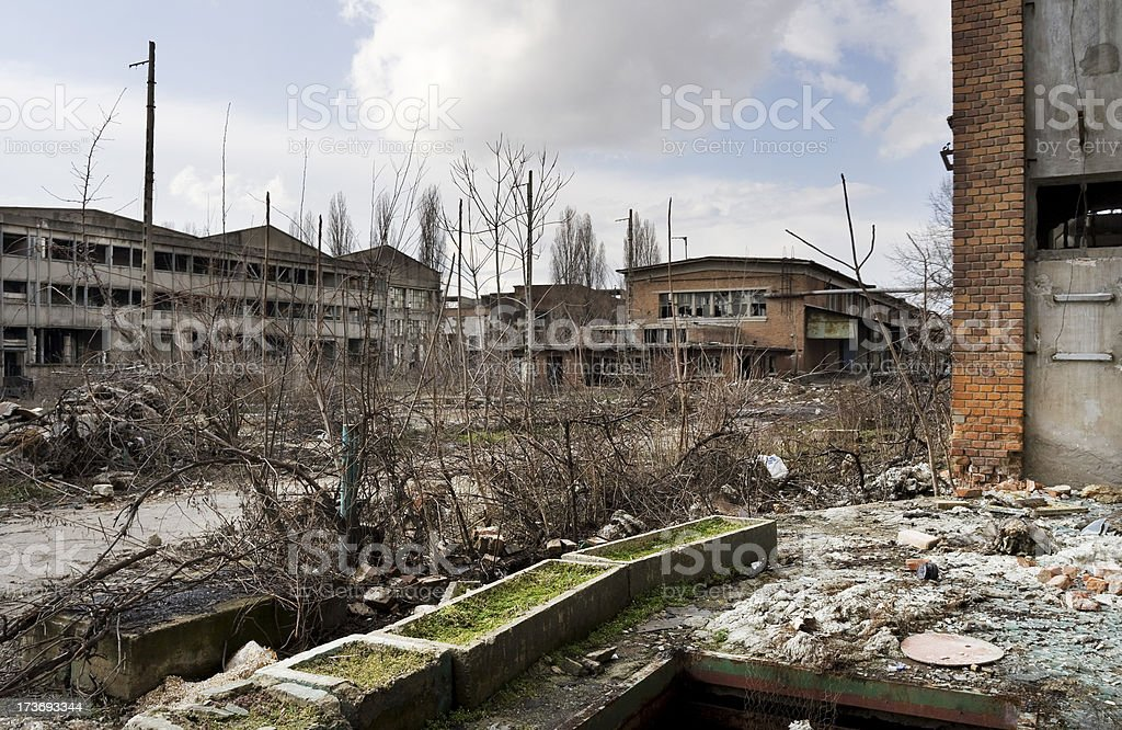 Destroyed industrial building and courtyard on crisis time stock photo