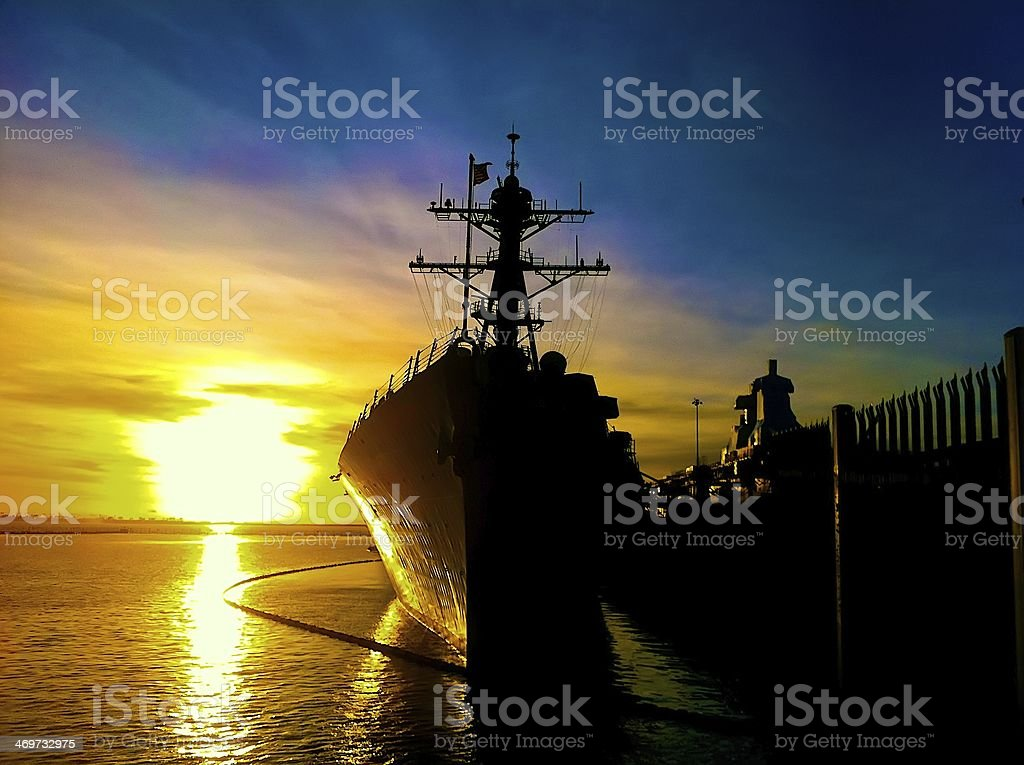destroyer pier side at sunset stock photo