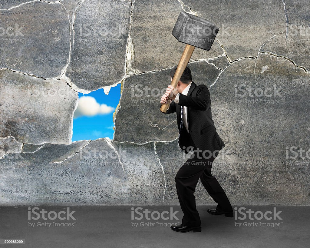 Destructing the wall with a large hammer stock photo