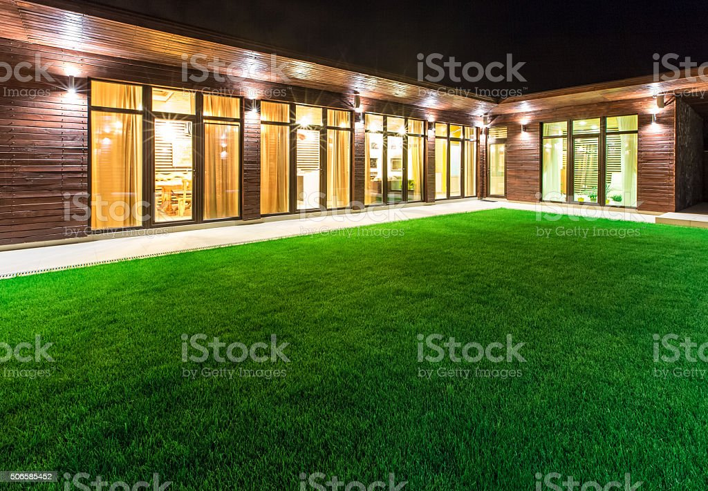 Detached house at night view from outside the rear courtyard. stock photo
