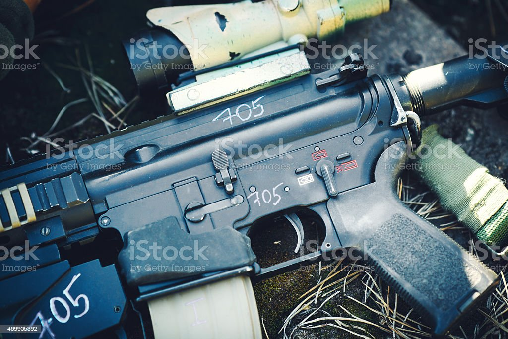 Detail automatic rifle weapons lying on the ground stock photo