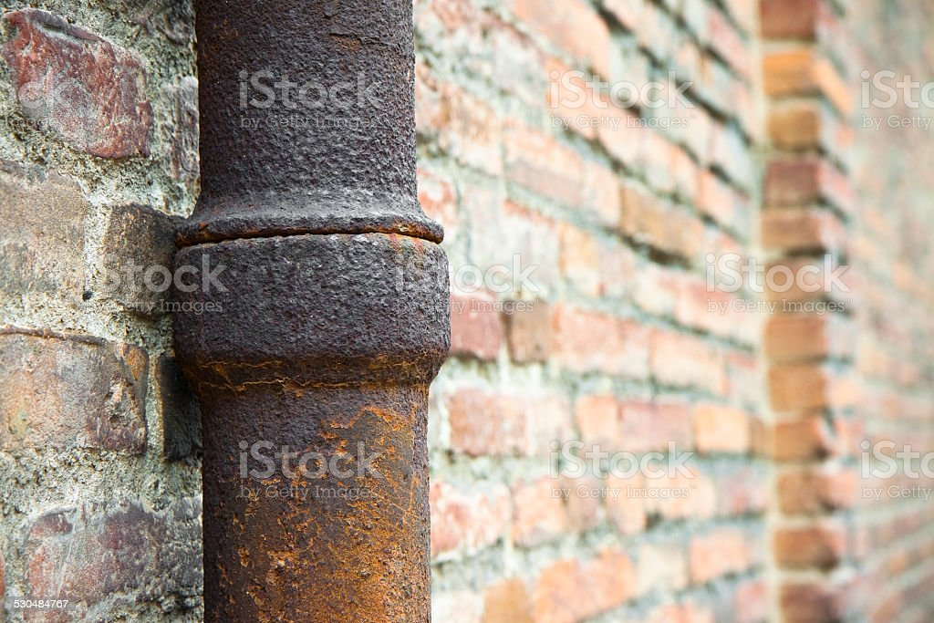 Detail of a downpipe against a brick wall stock photo