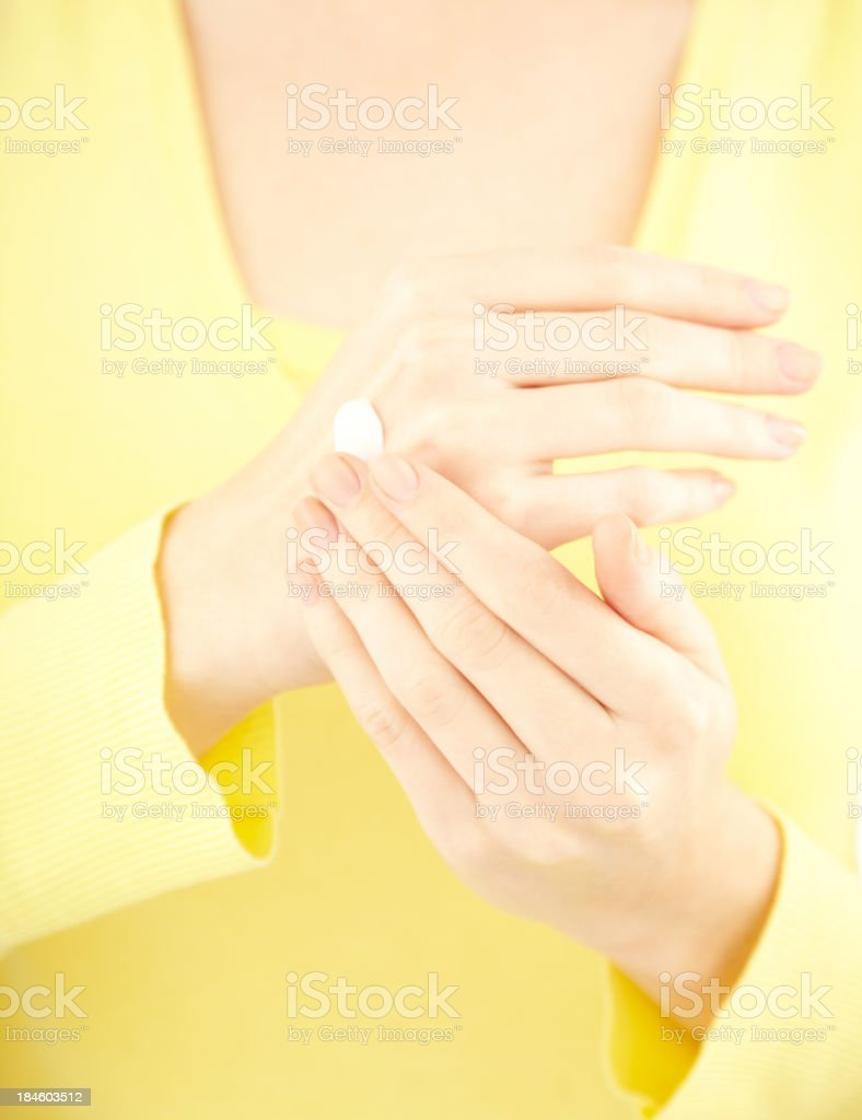 Detail of a girl applying cream to her hands royalty-free stock photo