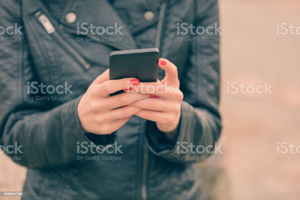 Detail of a girl holding a cellphone outdoors. stock photo