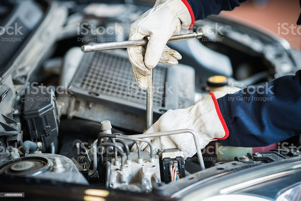 Detail of a mechanic at work on car engine stock photo