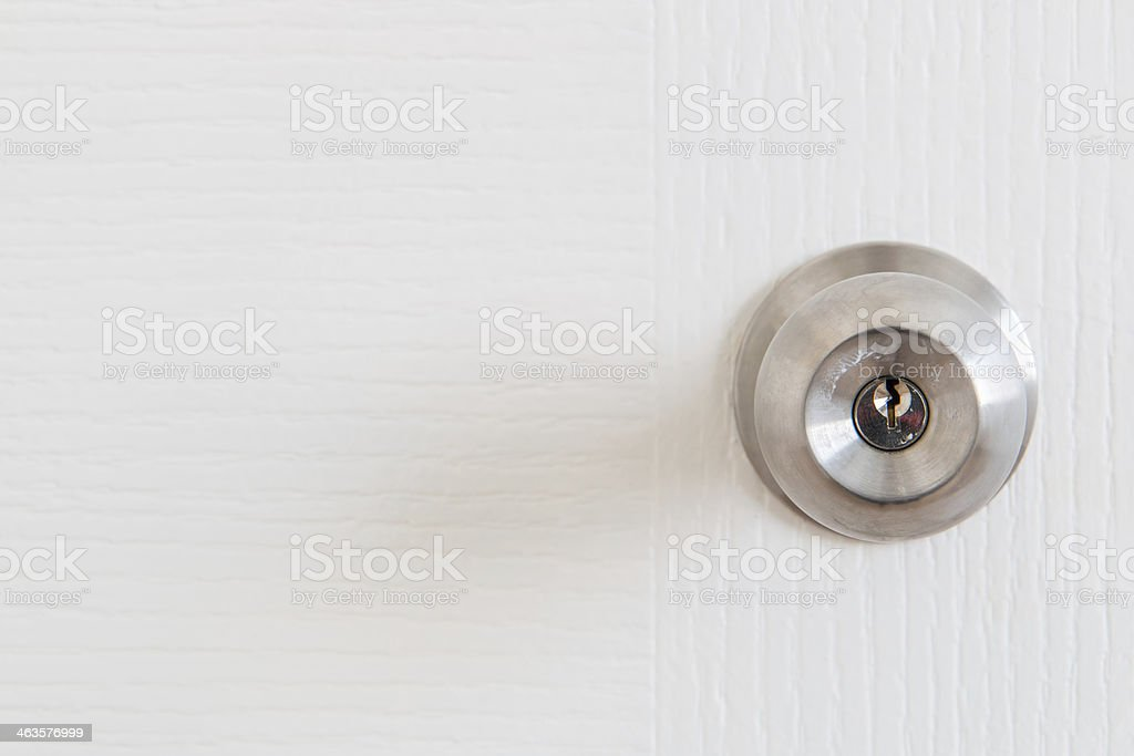 Detail of a metallic knob on white door stock photo