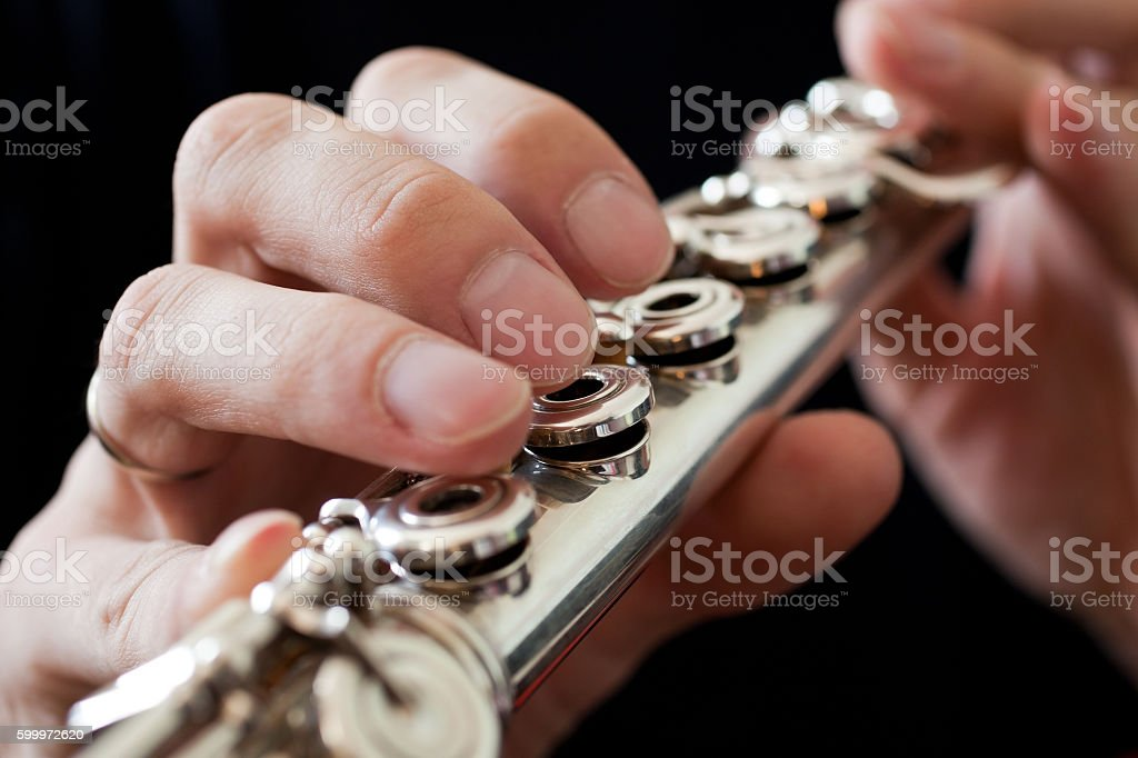 Detail of a musician flute in his hands closeup stock photo