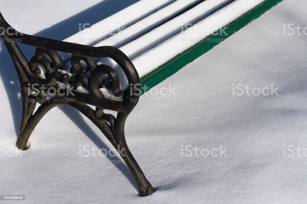 detail of a park bench in winter stock photo