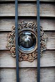 detail of a peephole in an old wood door