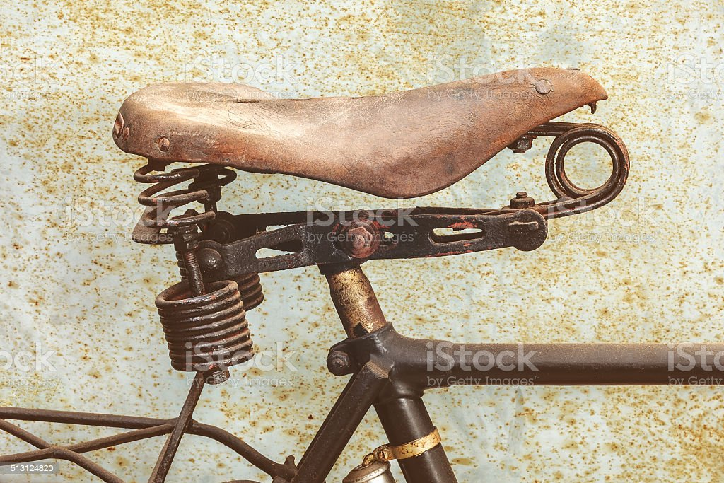 Detail of a rusted ancient bicycle with leather seat stock photo