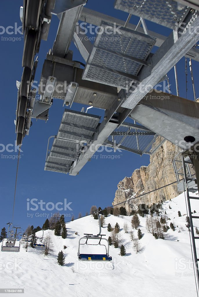 Detail of a ski resort chair lift against blue sky. royalty-free stock photo