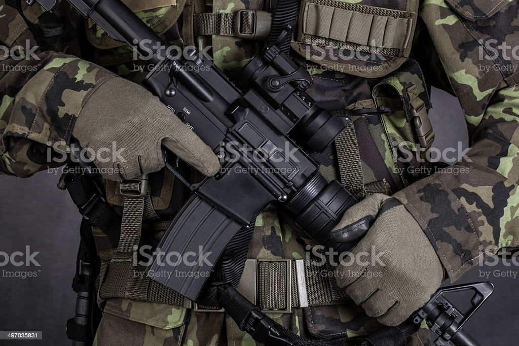 Detail of a soldier holding modern weapon M4 stock photo
