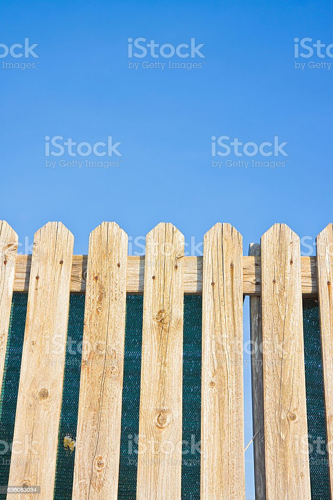 Detail of a wooden fence built with spiky wooden boards stock photo