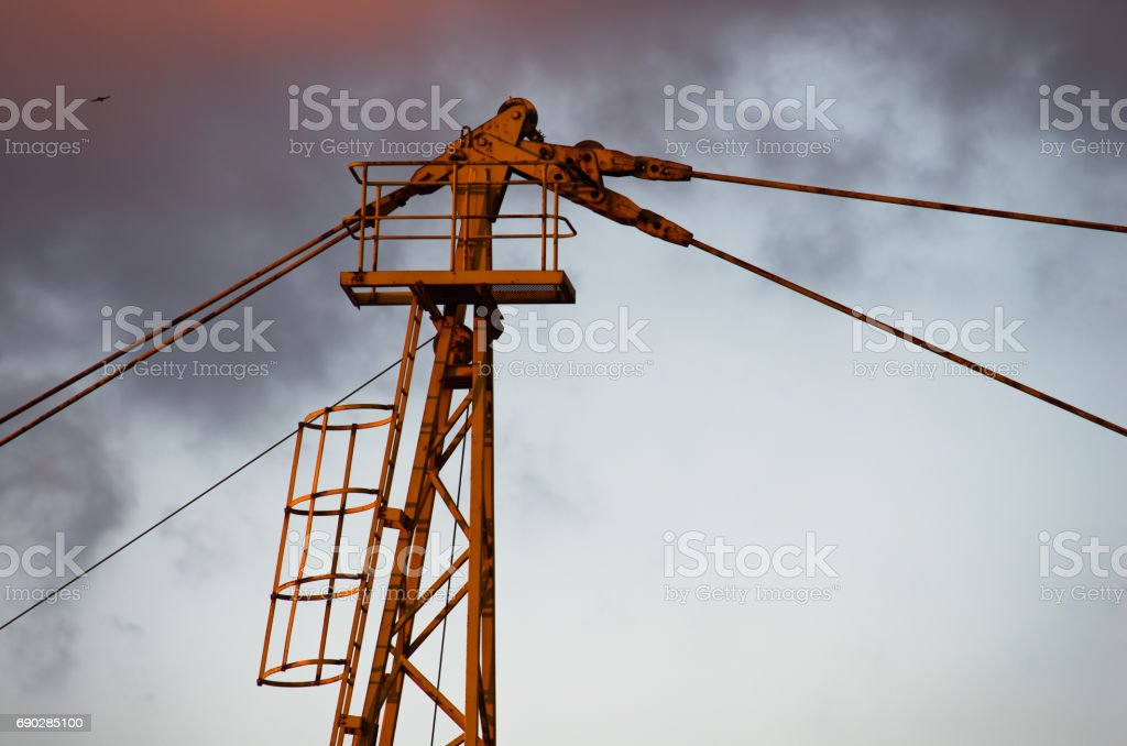 Detail of a yellow construction crane against cloudy sky at sunset in Belgrade stock photo
