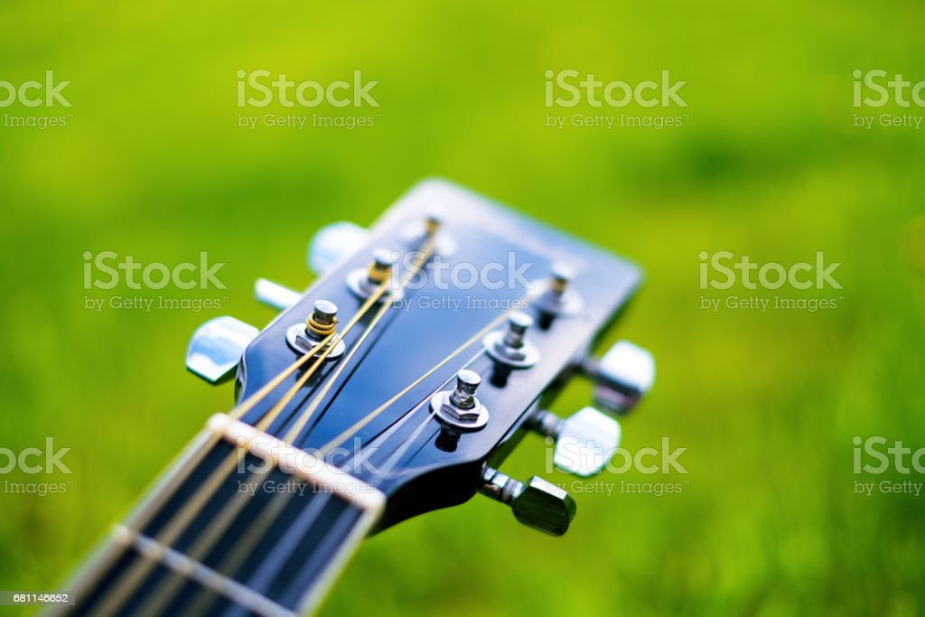 Detail of acoustic guitar on a grass. Natural background with flowers, grass and sun. Musical instrument. stock photo