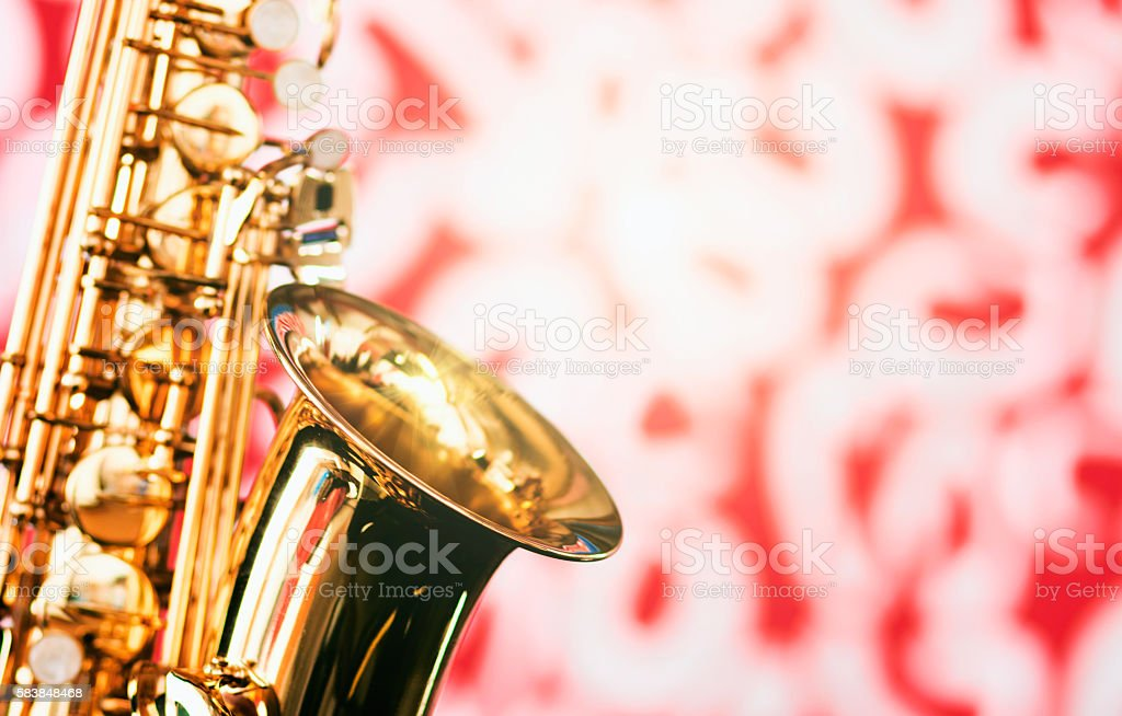 Detail of alto saxophone on defocused red-and-white background stock photo
