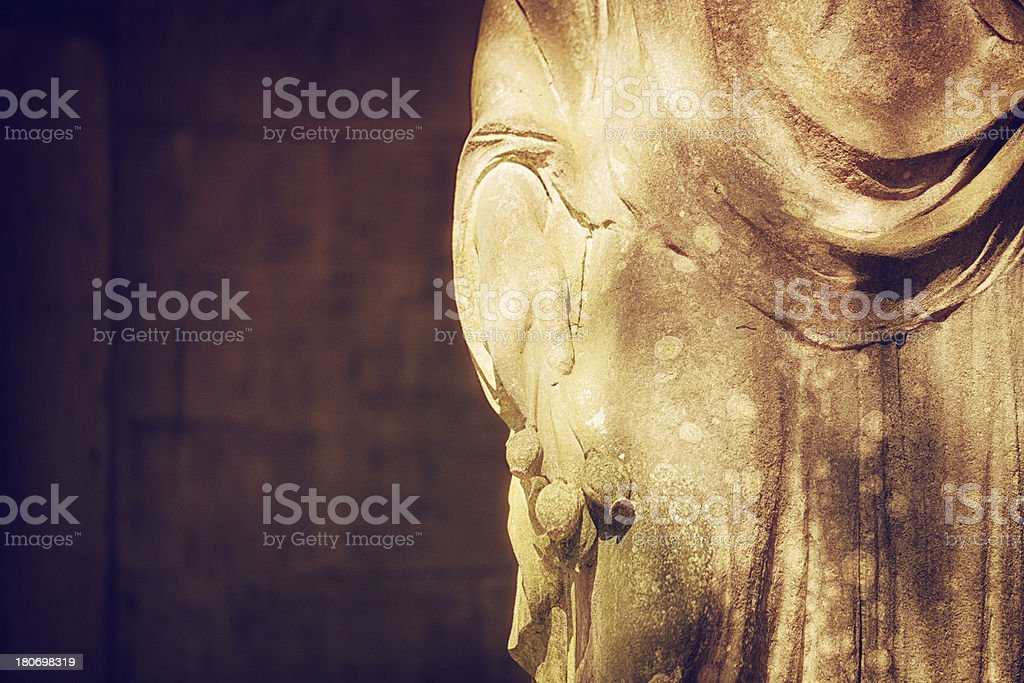 Detail of an old statue with flowers royalty-free stock photo