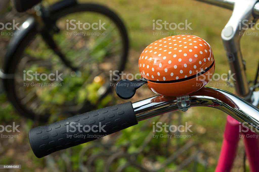 Detail of an orange bicycle ring bell stock photo