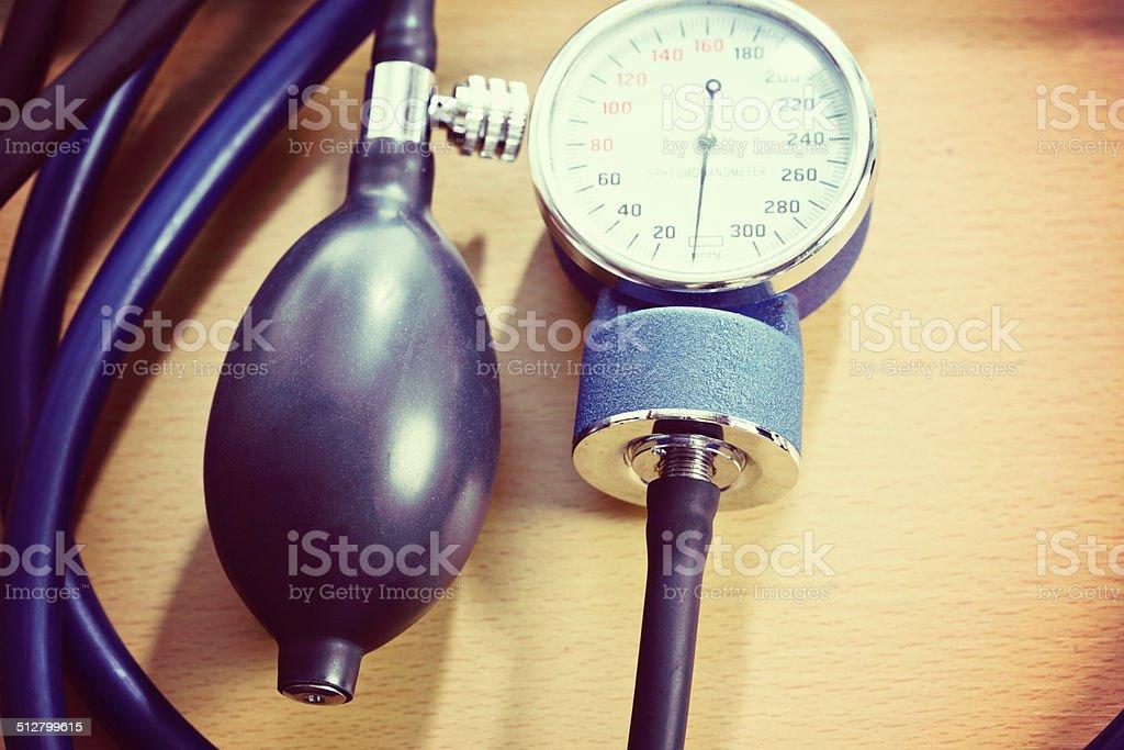 Detail of blood pressure meter on wooden desk stock photo