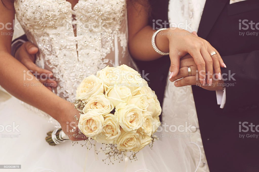 Detail of bride's roses bouquet and hands holding stock photo