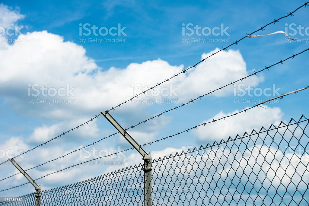 detail of fence with barbwire and blue sky stock photo