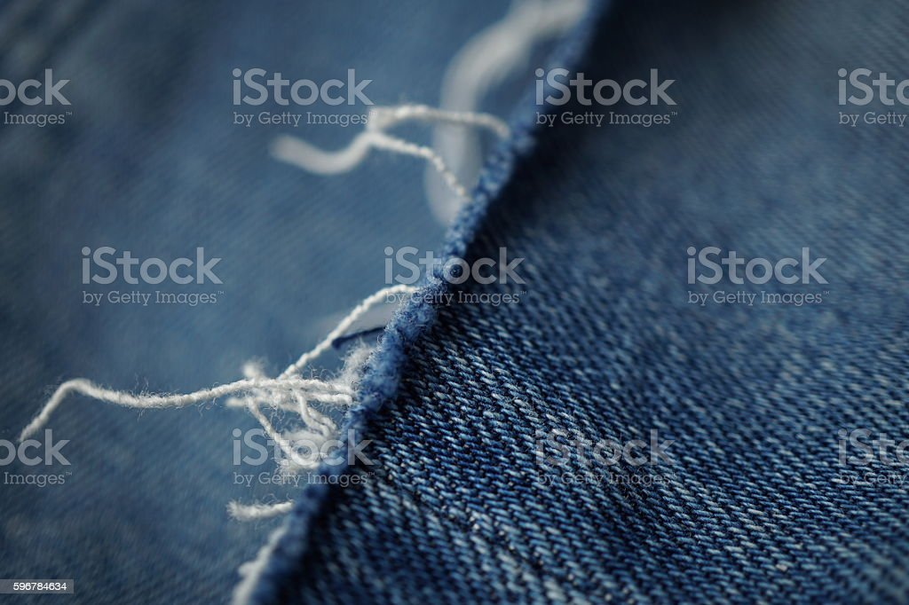 Detail of frayed threads at the end of blue shorts stock photo