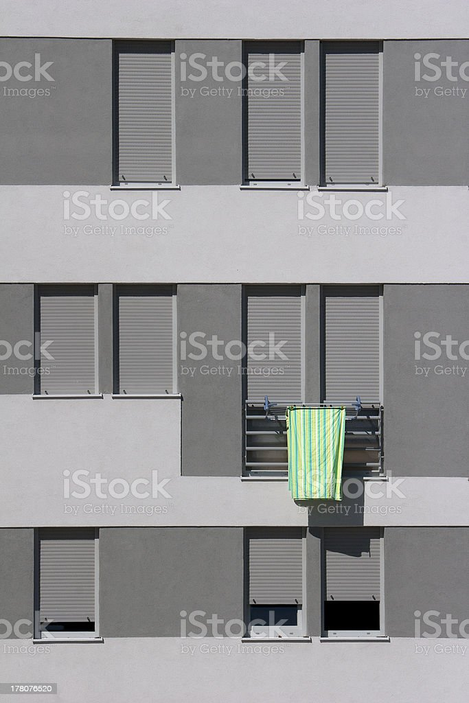 Detail of gray facade with colorful sheet on the window royalty-free stock photo