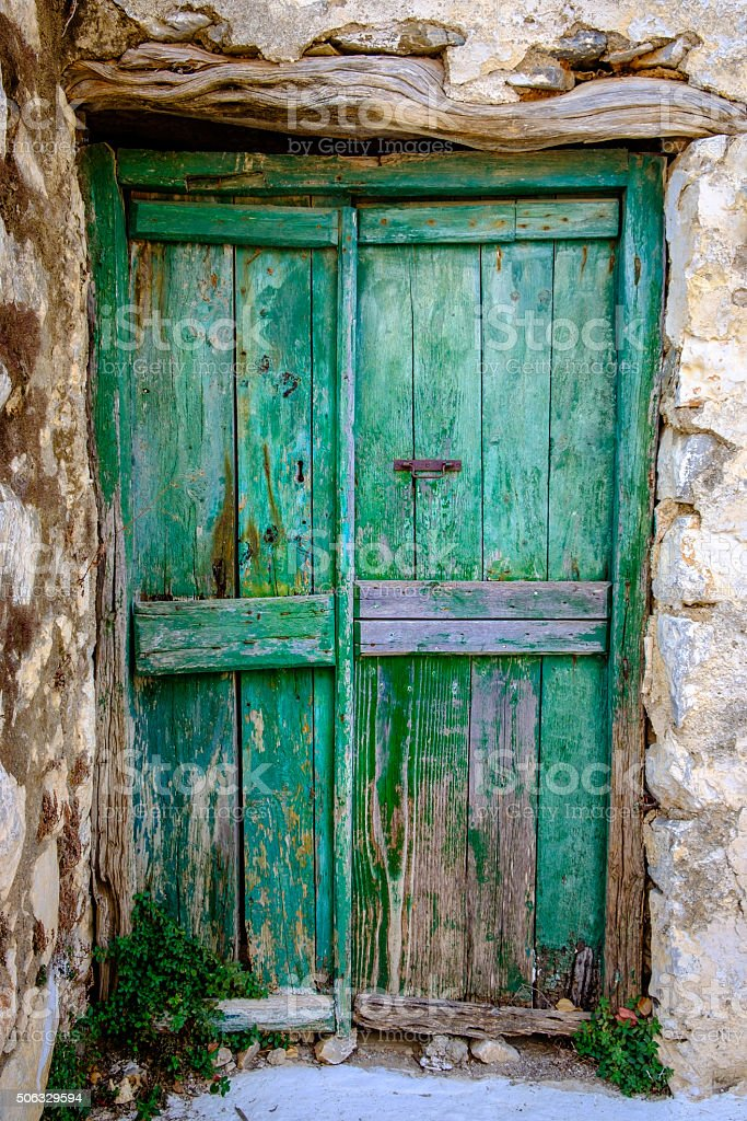Detail of green wooden door in vintage stone wall stock photo