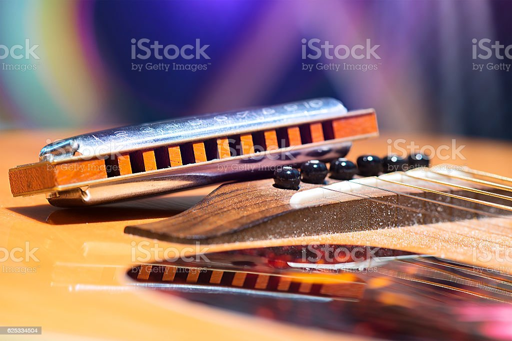 Detail of guitar strings with supported harmonica for country mu stock photo