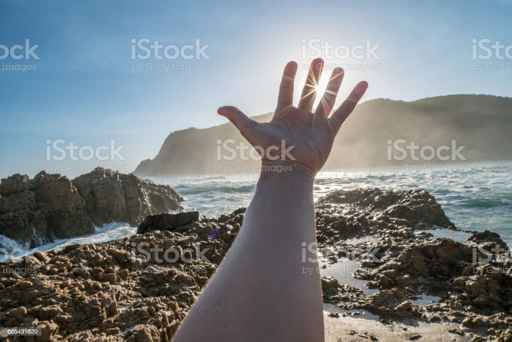 Detail of hand stretched to cup rays of sunrise – Foto