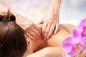 Detail of hands massaging female neck.