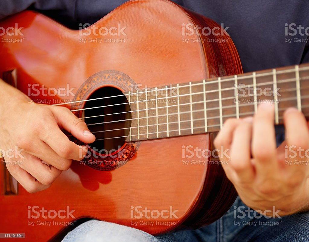 Detail of hands of a boy playing the guitar royalty-free stock photo