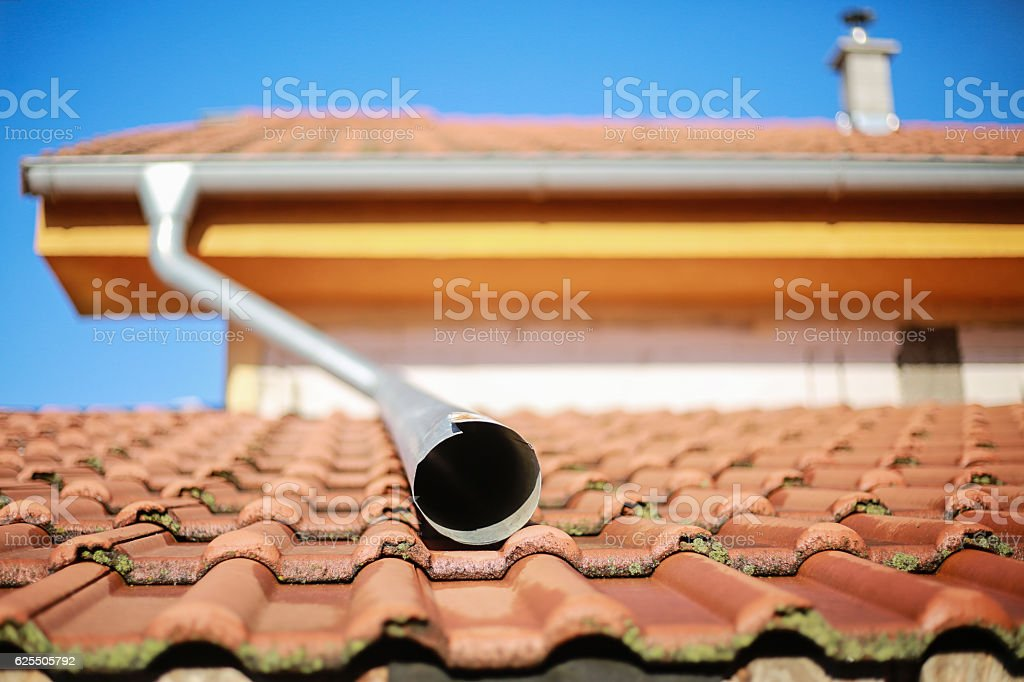 Detail of house roof with water spout and small chimney stock photo
