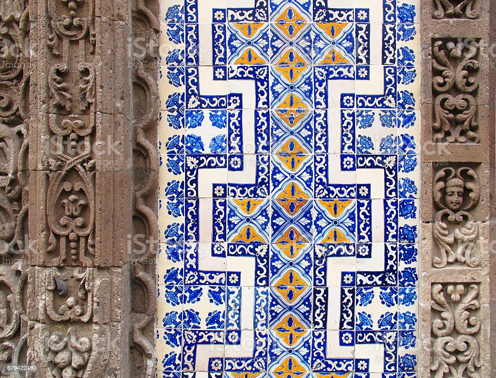 Detail of Mexican building with carved stone and painted tiles stock photo