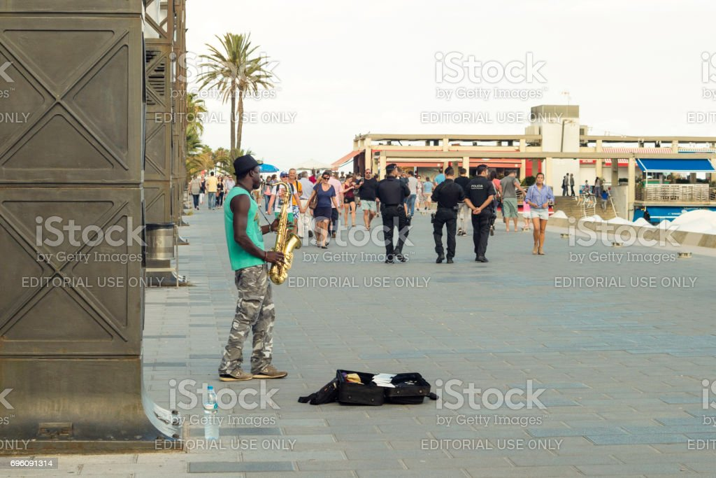 Detail of musician playing saxophone on the streets with group of tourists and police at Por Olimpic in Barcelona, Spain stock photo